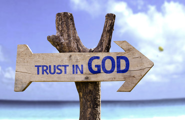 Trust in God wooden sign with a beach on background