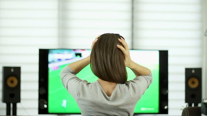 Female football fan expressing disappointment, rear view
