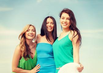 smiling girls walking on the beach