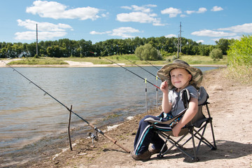 Boy sitting with fishing rods on the bank of the pond.