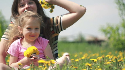 Mom and daughter throw their bouquet of dandelions