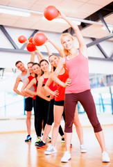 group of smiling people working out with ball