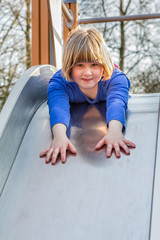 Young girl liying forward on slide