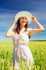 smiling young woman in straw hat on cereal field