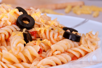 Pasta with tomato, garlic and black olives, sprinkled with chees