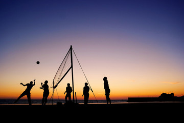 Silhouettes of a group playing beach volleyball on the beach