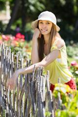 woman in hat near fence
