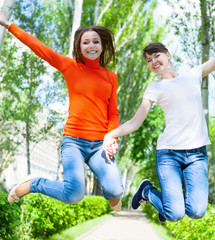 Happy young teen girls jumping it the park