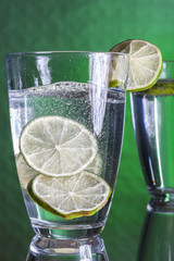 glass of water and lime on a green background
