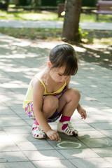 Девочка рисует мелом на тротуарной плитке