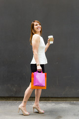 Woman with shopping bags and coffee in the city