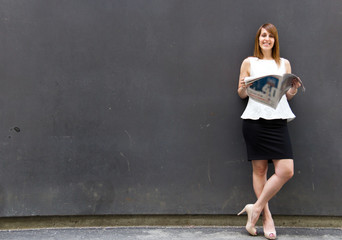 Business woman reading the newspaper leaning against the wall