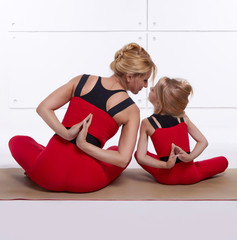 Mother daughter doing yoga exercise fitness gym sports paired