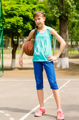 Beautiful smiling girl standing with a basketball in outdoor