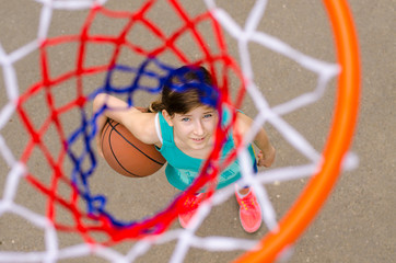 Young girl standing under hoop