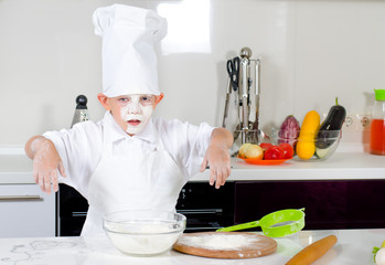 Cute little boy chef in the kitchen