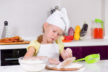 Smiling little girl in a chefs uniform