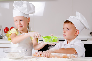 Two happy young children learning to bake