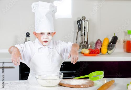 Cute little boy chef in the kitchen