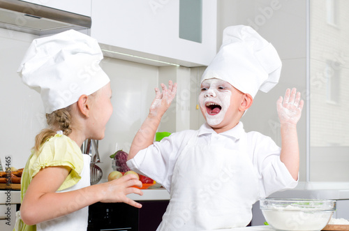 Happy little boy and girl baking in the kitchen