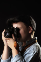 Boy with old camera. Dark background. Retro style.