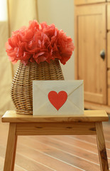 Vase basket with red tissue paper pompom flower and love letter