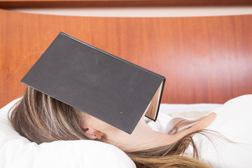 Young girl sleeping with book on her face