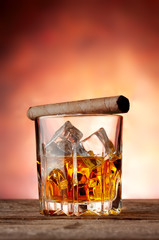 Faceted glass with whiskey and cigar
