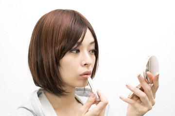 口紅をつける女性