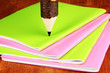 Colorful wooden pencil with exercisebooks on wooden table