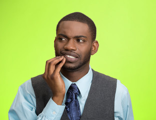 Man with tooth ache, pain isolated on green background