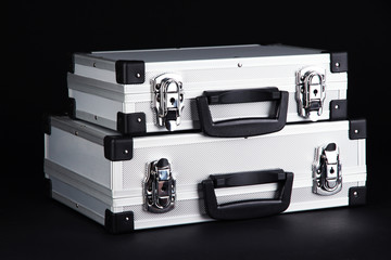 Silvery suitcases on black background