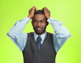 Portrait Stressed man pulling his hair out, green background