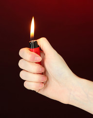 Burning lighter in female hand, on dark red background