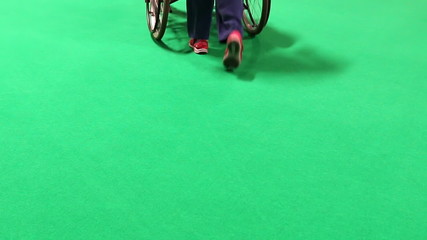 Woman pushing wheelchair isolated on green