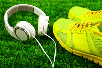 Sport shoes and headphones on green grass background