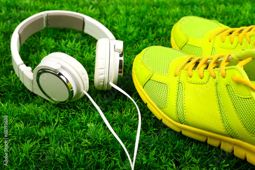 canvas print picture Sport shoes and headphones on green grass background