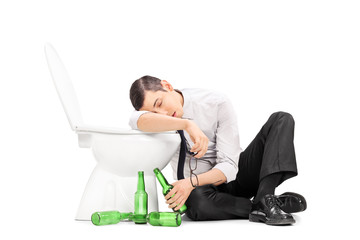 Male alcoholic sleeping on a toilet