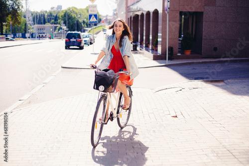 Leinwandbild Motiv Beautiful woman in dress with bike