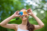 Sport woman with badminton racket and shuttlecock near her eyes