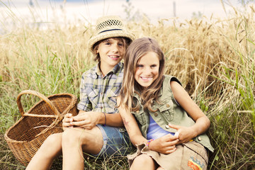 Friends picnicking together in a field of wheat