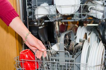 hausfrau räumt die spülmaschine aus