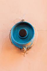 Campanello blu con bottone nero su sfondo color salmone