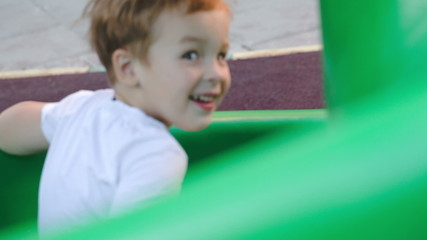 Happy child on slide outdoor