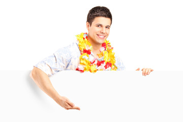 Young man with lei around his neck behind a panel