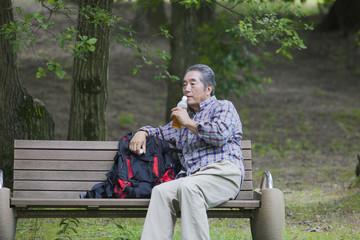 ベンチで休憩するシニアの男性