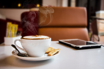 coffee and tablet on table in cafe