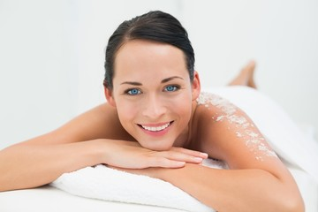 Peaceful brunette smiling at camera with salt scrub on back