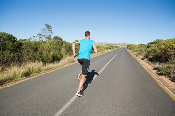 Fit man jogging on the open road