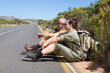 Hiking couple sitting on the side of the road
